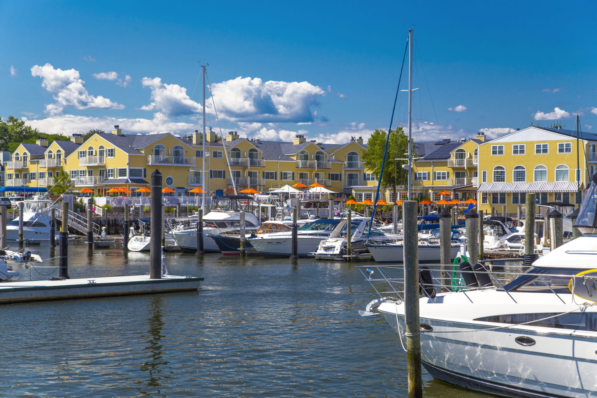 Boats in a marina in front of Saybrook Point Resort & Marina on a sunny day.