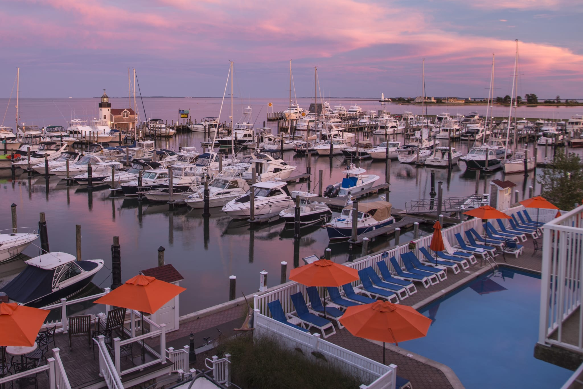 View from a balcony overlooking a marina at sunset.