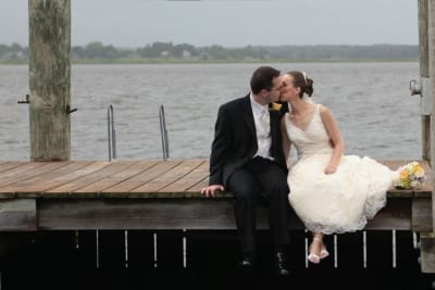 Bride and groom kissing on dock.