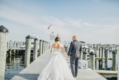 Bride and groom walk on the docks.