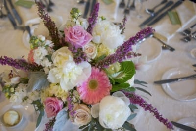 Bright floral pink purple wedding table arrangement.