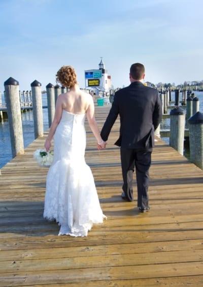 Bride and groom walking on marina dock.