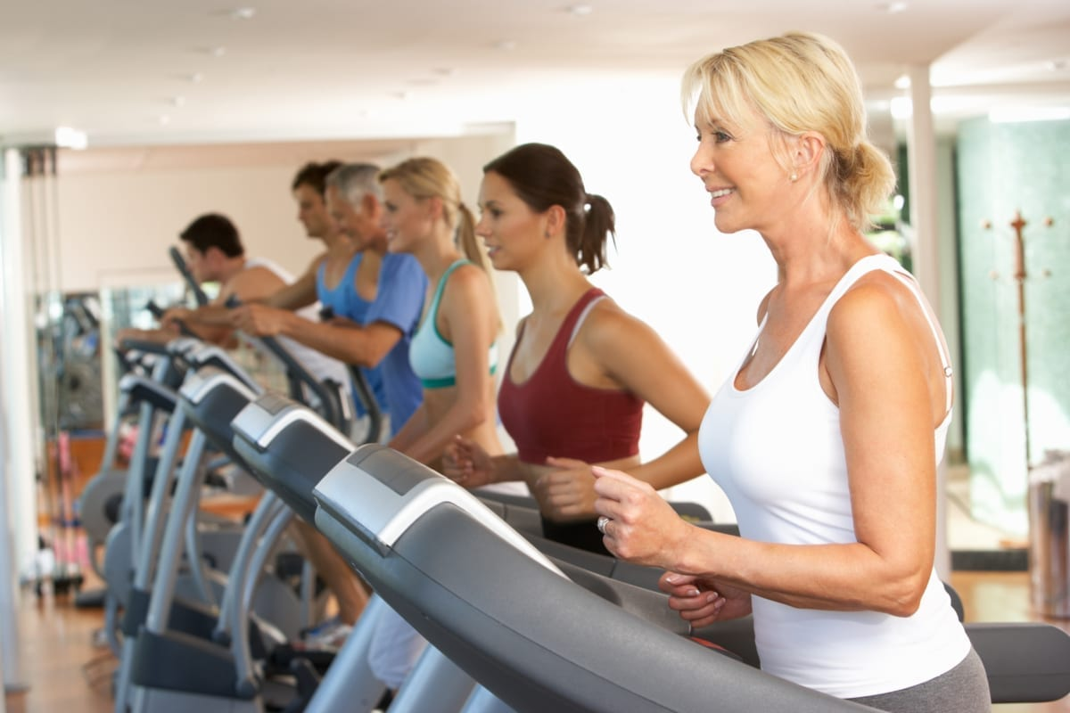 Senior Woman On Running Machine In Gym.