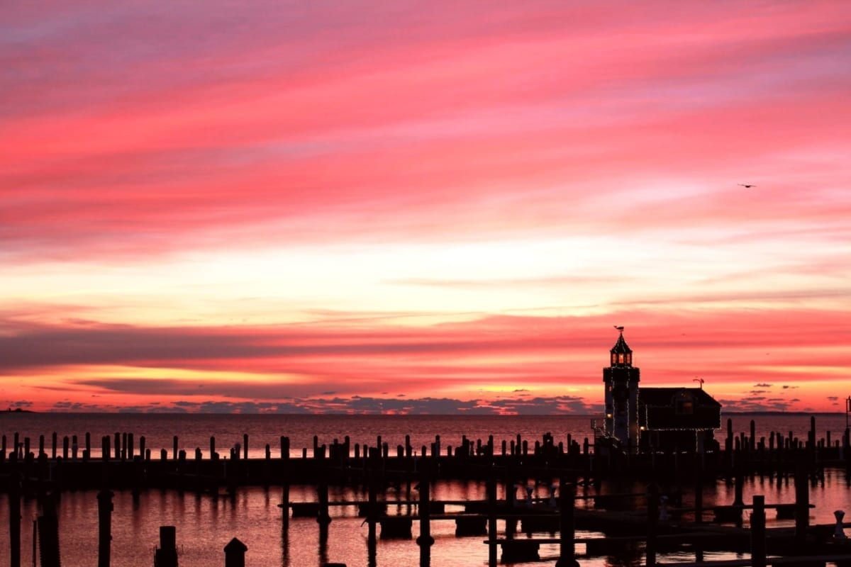 Sunset over Saybrook Point marina and lighthouse with pink clouds.