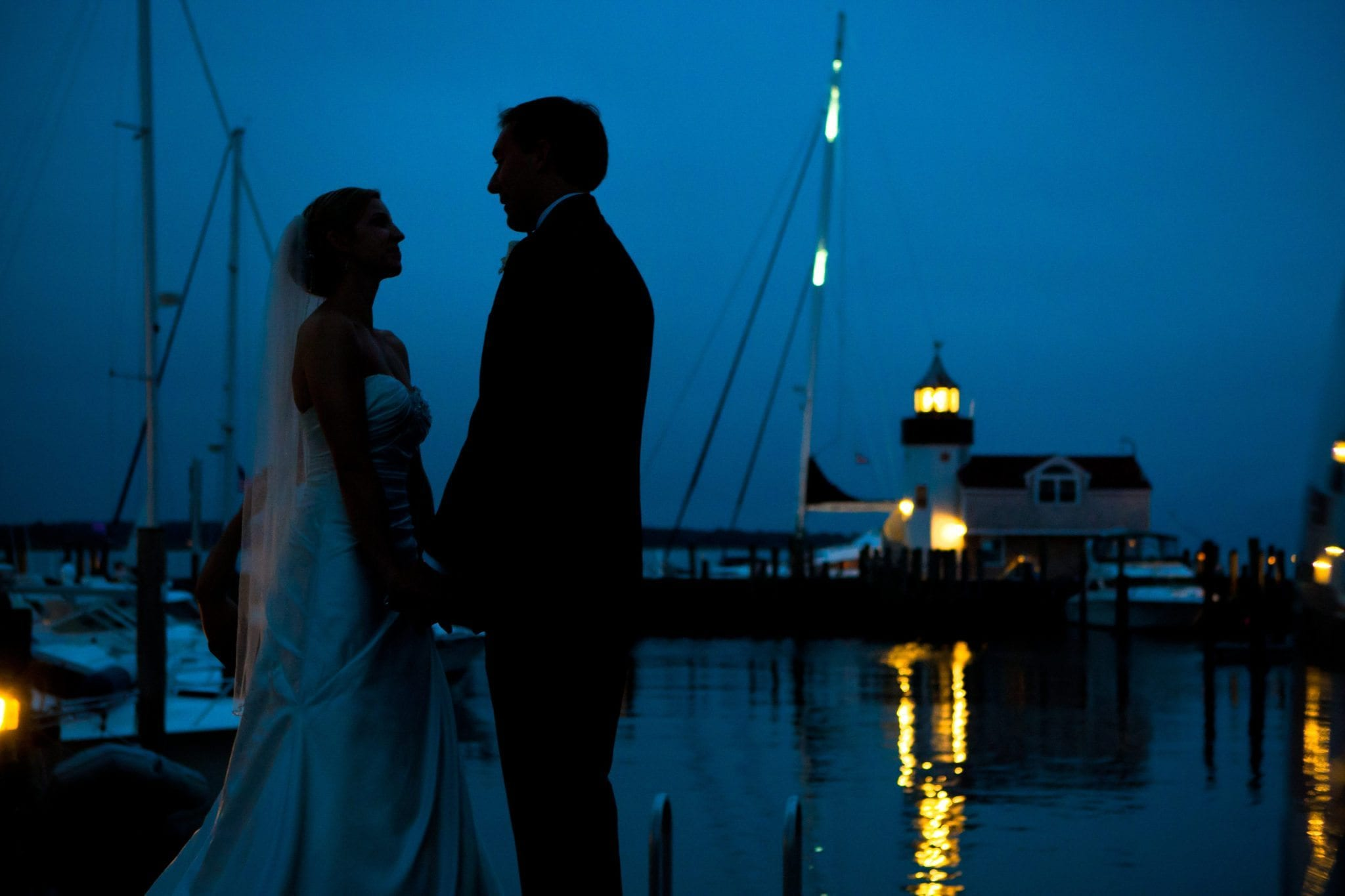 Bride and groom standing near marina at night with lighthouse in background.