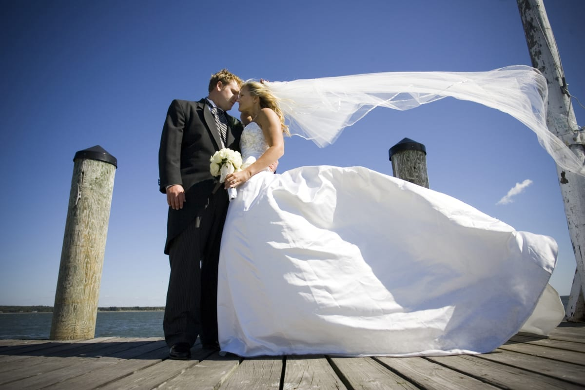 Bride and groom posing on dock wit veil and gown blowing in wind.