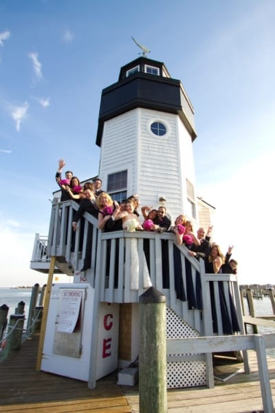 Wedding party posing on stairs of lighthouse.
