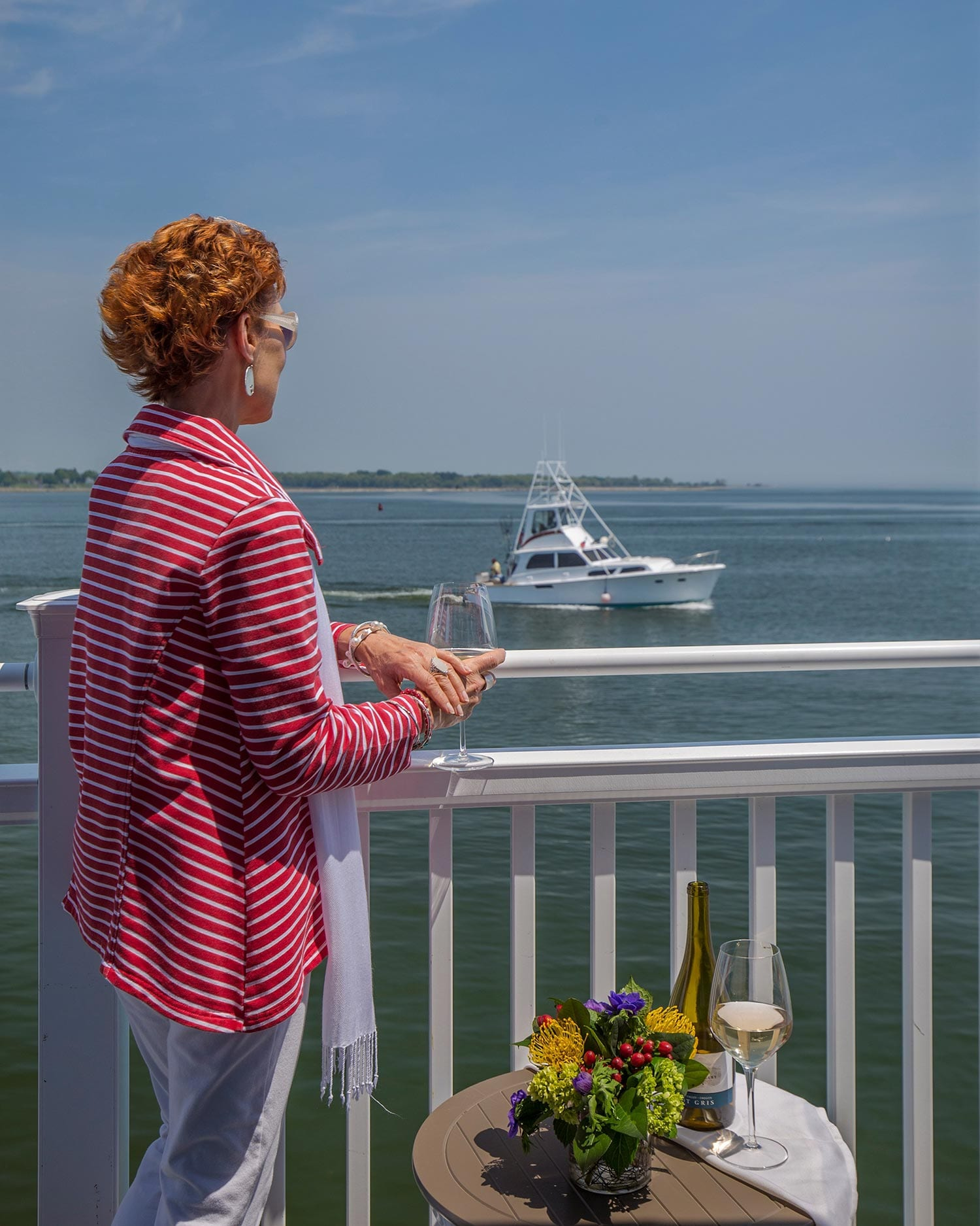 OIder Red Haired Women On Balcony Looking At Boats On The Connecticut River