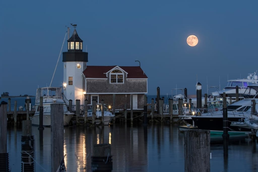 Saybrook Point Inn lighthouse and marina on still night with moon above