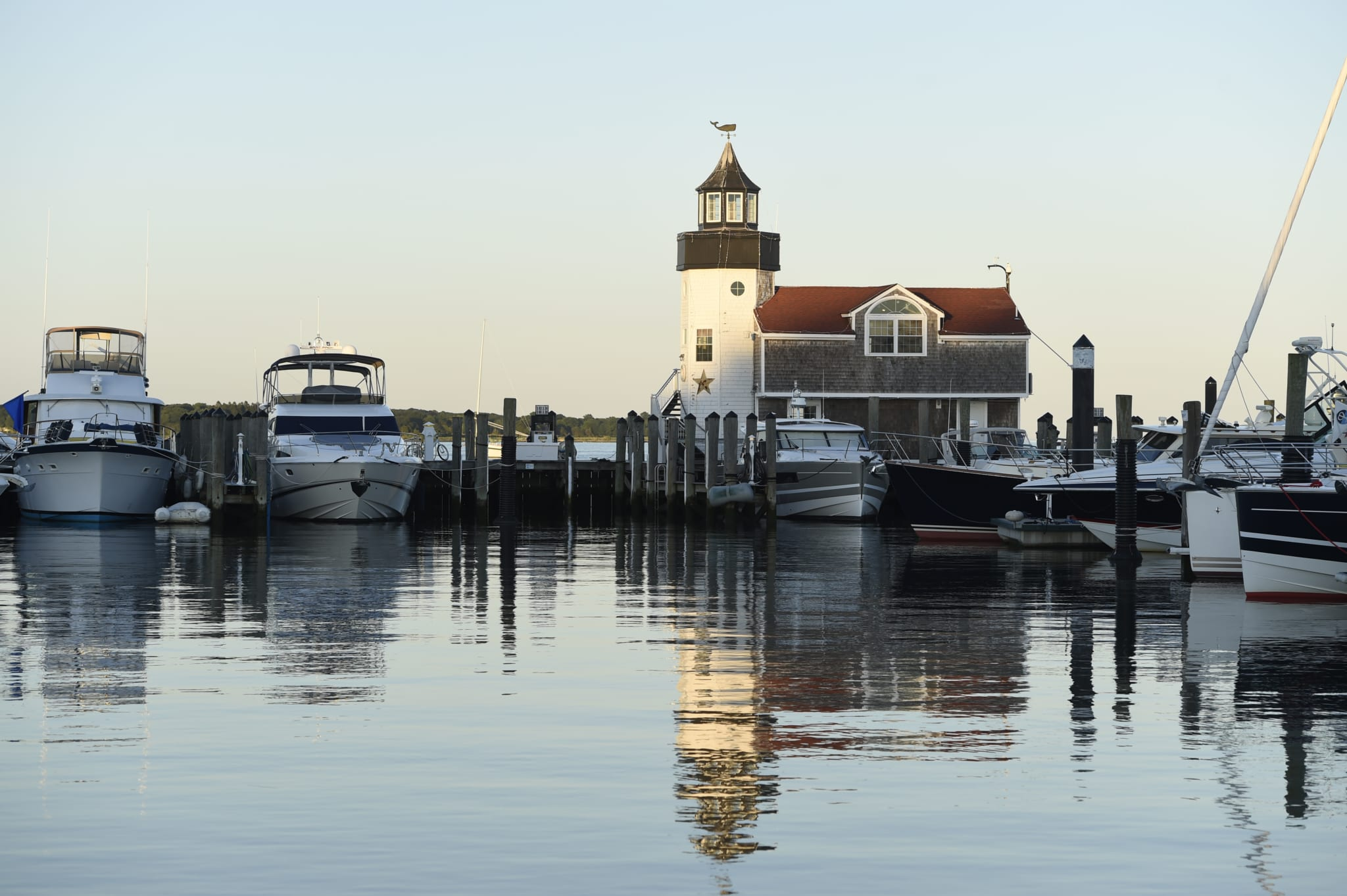 Lighthouse and boats in marina.