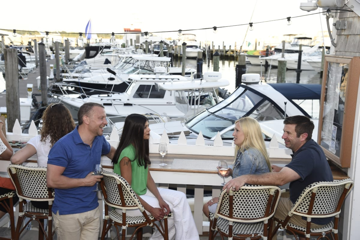 People enjoying drinks at outdoor marina bar.