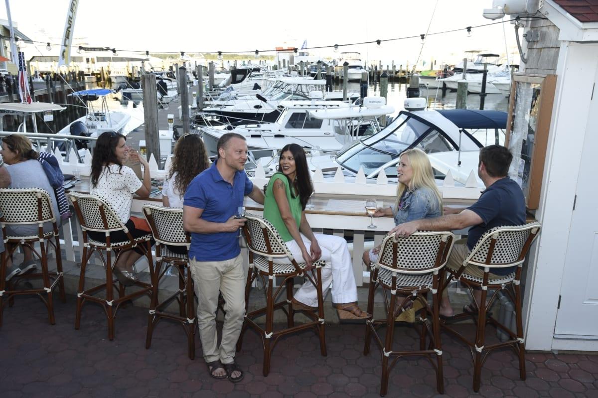 People enjoying drinks at outdoor area of marina bar.