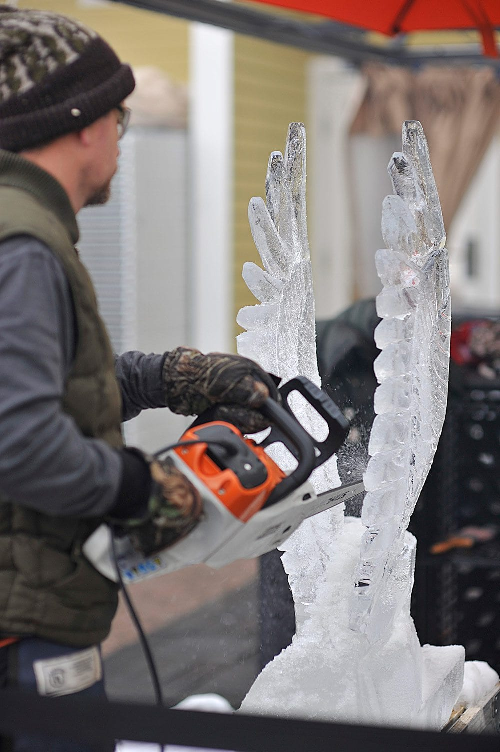 Ice sculptor using chainsaw to create ice bird.