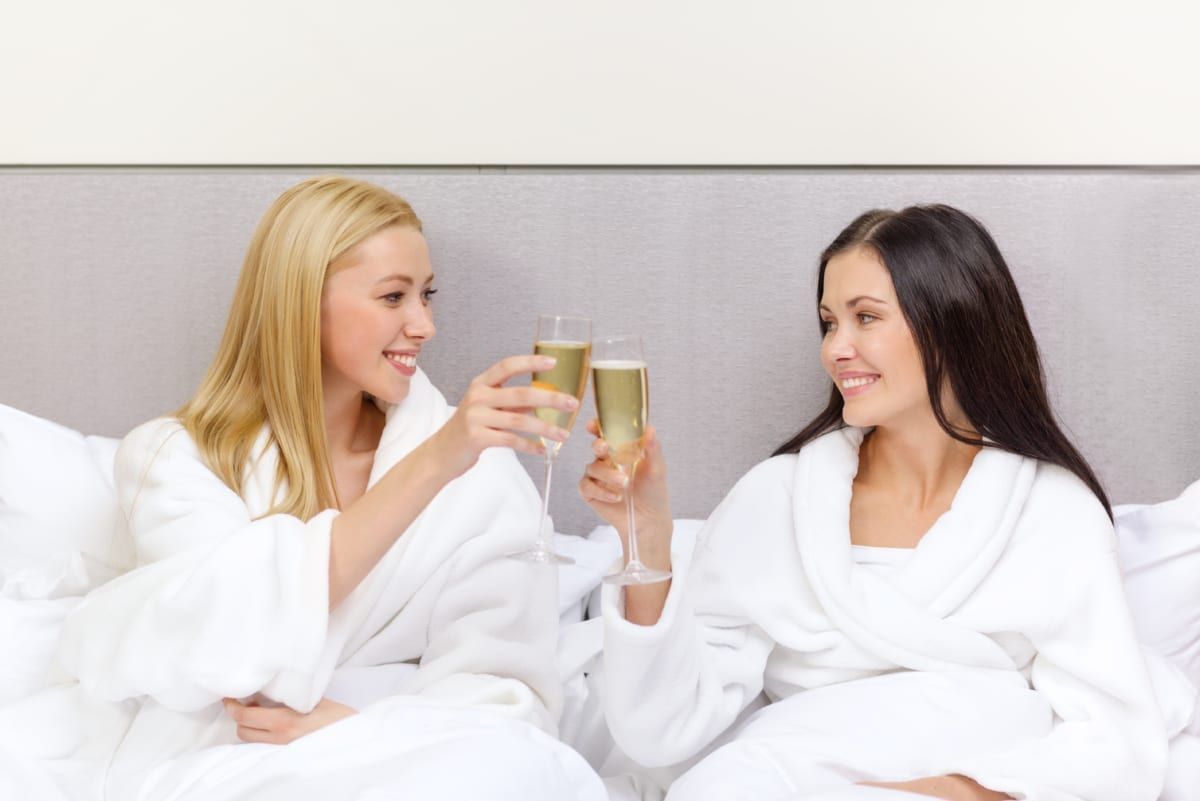 Women in spa robes holding champagne glasses.