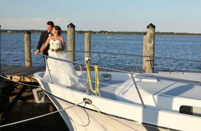 Bride and groom standing on bow of boat.
