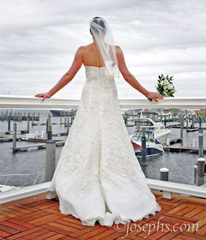 Bride looking out on harbor.