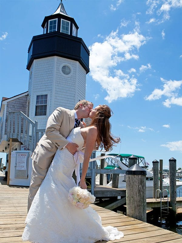 Bride and groom kissing near lighthouse.