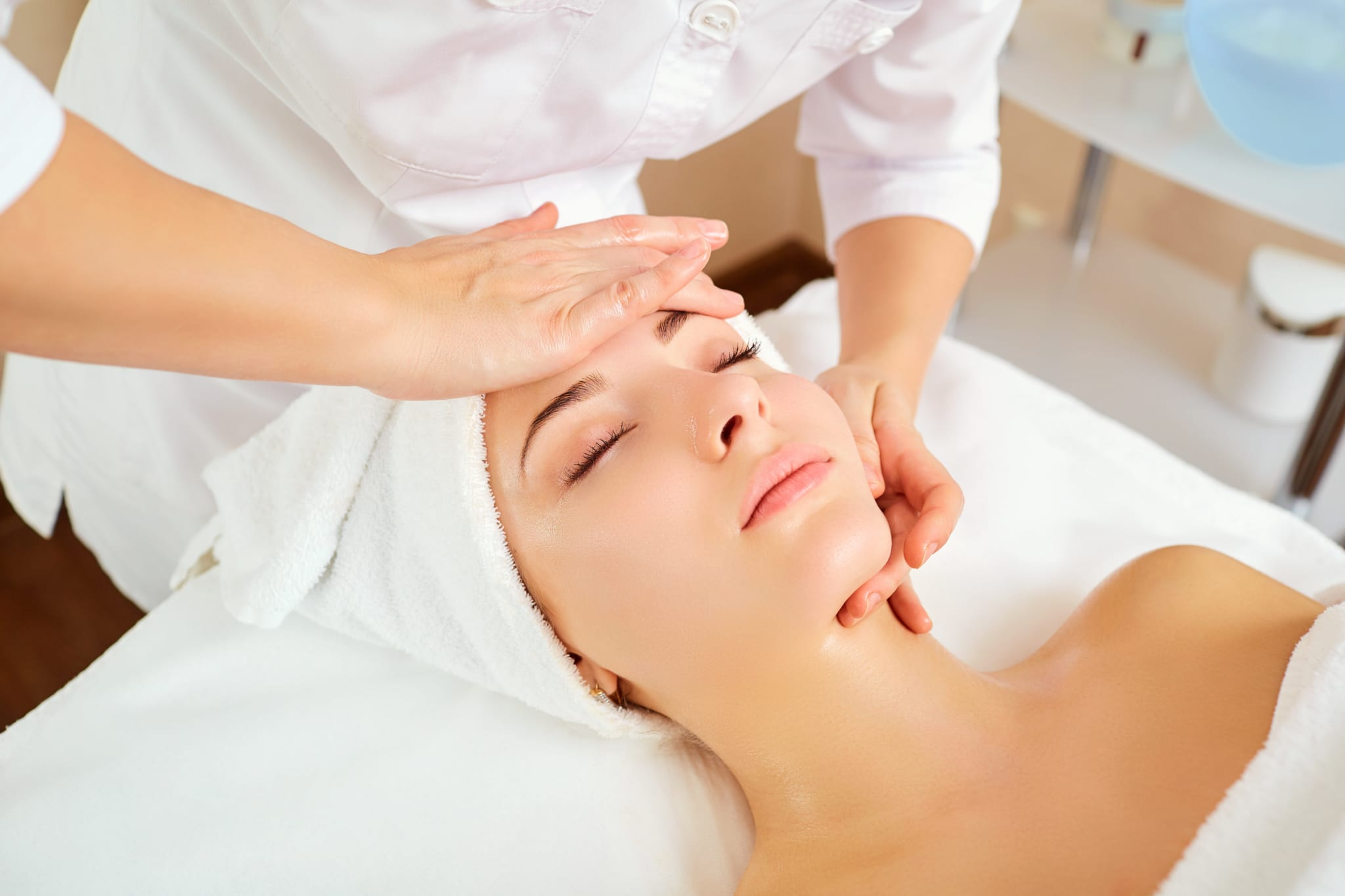 Woman at a facial massage at a spa salon.