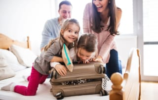 Photo of a Family Packing. Click Here to Learn How to Travel with Kids