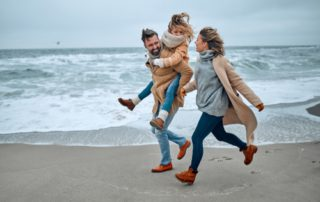 A mom, dad, and daughter run on the beach during the winter in Old Saybrook, CT.